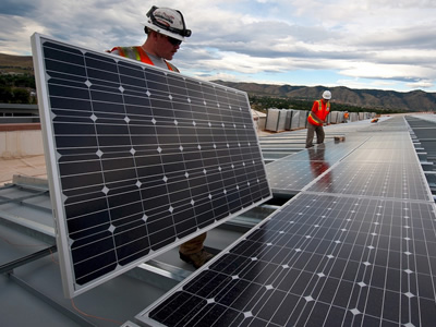 Employees of a solar company are setting up a solar panel array