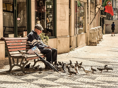 Old man enjoys company of pigeons.