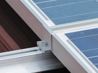 Solar panel attached to the railing by a clamp.